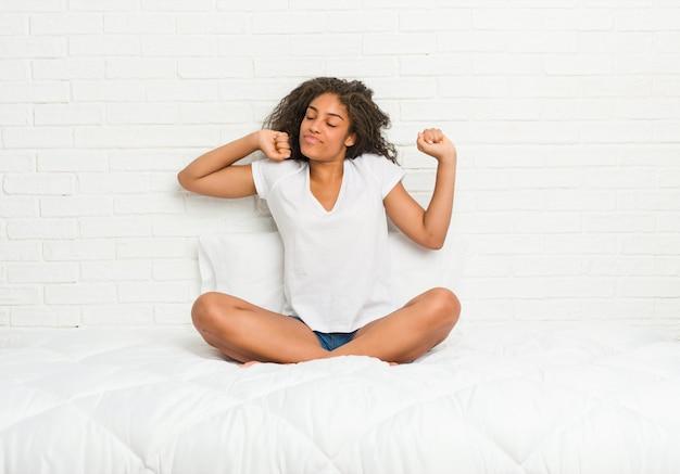 Młoda amerykanin afrykańskiego pochodzenia kobieta ono rozciąga na łóżku