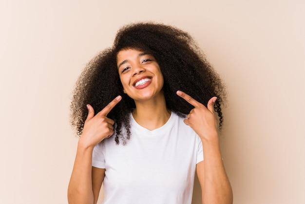 Młoda amerykanin afrykańskiego pochodzenia kobieta ono uśmiecha się, wskazujący palce przy usta.