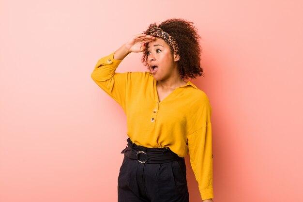 Młoda amerykanin afrykańskiego pochodzenia kobieta patrzeje daleki przeciw różowemu tłu utrzymuje rękę na czole.