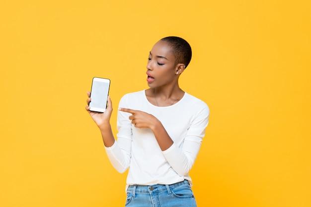 Młoda amerykanin afrykańskiego pochodzenia kobieta patrzeje telefon komórkowego odizolowywającego na kolor żółty ścianie i wskazuje