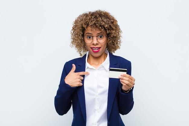 Młoda amerykanin afrykańskiego pochodzenia kobieta patrzeje zszokowany i zdziwiony z usta szeroko otwarty, wskazujący ja z kartą kredytową