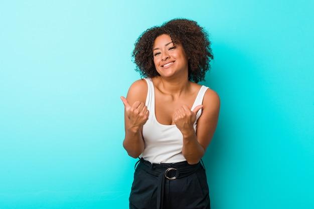 Młoda amerykanin afrykańskiego pochodzenia kobieta podnosi oba aprobaty, uśmiechnięty i ufny.