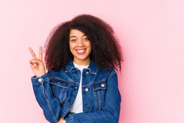 Młoda amerykanin afrykańskiego pochodzenia kobieta pokazuje numer dwa z palcami.