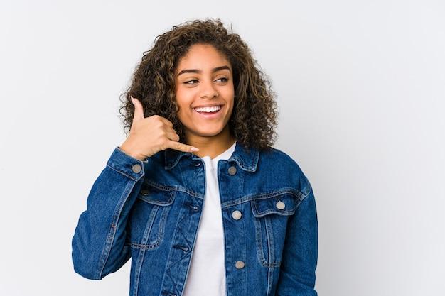Młoda amerykanin afrykańskiego pochodzenia kobieta pokazuje telefonu komórkowego wezwania gest z palcami.