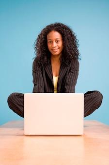 Młoda amerykanin afrykańskiego pochodzenia kobieta pracuje na laptopie