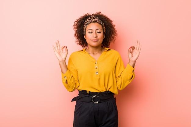Młoda amerykanin afrykańskiego pochodzenia kobieta przeciw menchii relaksuje po ciężkiego pracującego dnia, wykonuje joga.