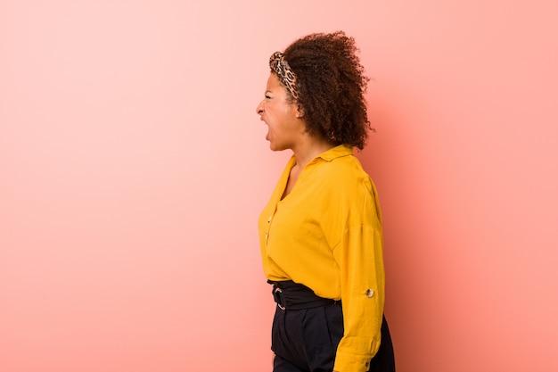 Młoda amerykanin afrykańskiego pochodzenia kobieta przeciw różowej ścianie krzyczy w kierunku pustej przestrzeni
