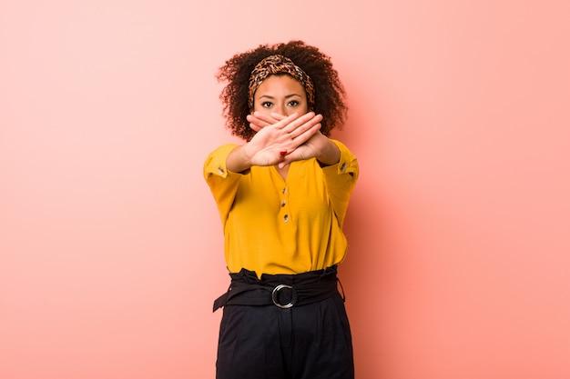 Młoda amerykanin afrykańskiego pochodzenia kobieta przeciw różowej ścianie robi zaprzeczeniu gestowi