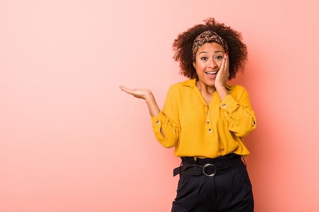 Młoda amerykanin afrykańskiego pochodzenia kobieta przeciw różowej ścianie trzyma kopii przestrzeń na dłoni, utrzymuje oddawał policzek. zaskoczony i zachwycony.