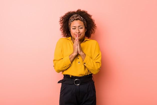 Młoda amerykanin afrykańskiego pochodzenia kobieta przeciw różowej ścianie trzyma ręki w modli się blisko usta, czuje się pewny.