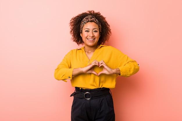 Młoda amerykanin afrykańskiego pochodzenia kobieta przeciw różowej ścianie uśmiecha się kierowego kształt z rękami i pokazuje.