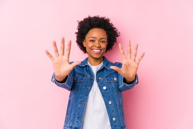 Młoda amerykanin afrykańskiego pochodzenia kobieta przeciw różowemu backgroound odizolowywał pokazywać liczbę dziesięć z rękami.