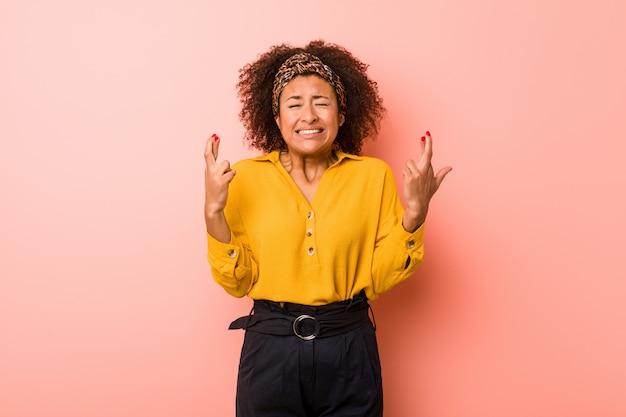 Młoda amerykanin afrykańskiego pochodzenia kobieta przeciw różowemu tłu krzyżuje palce dla mieć szczęście