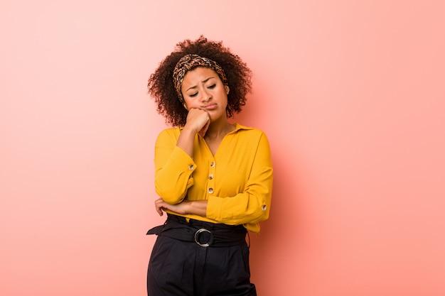 Młoda amerykanin afrykańskiego pochodzenia kobieta przeciw różowemu tłu, który czuje smutny i zadumany, patrzeje kopii przestrzeń.