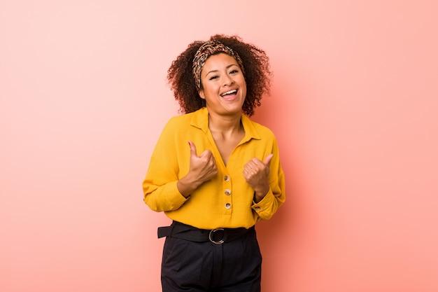 Młoda amerykanin afrykańskiego pochodzenia kobieta przeciw różowemu tłu podnosi oba aprobaty, uśmiechnięty i ufny.