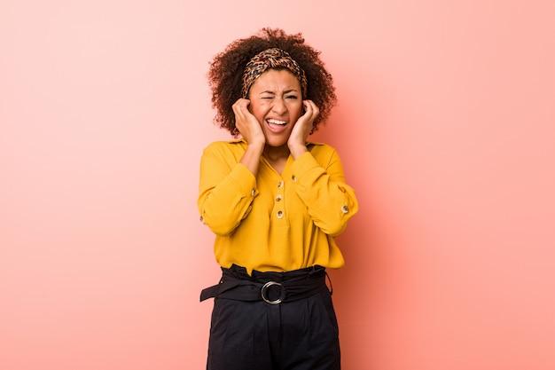 Młoda amerykanin afrykańskiego pochodzenia kobieta przeciw różowemu tłu zakrywającemu ucho z rękami.