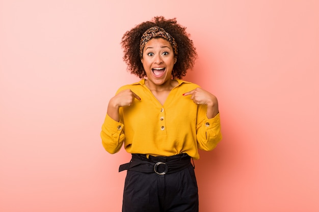 Młoda amerykanin afrykańskiego pochodzenia kobieta przeciw różowemu tłu zaskakiwał wskazywać palcem, ono uśmiecha się szeroko.