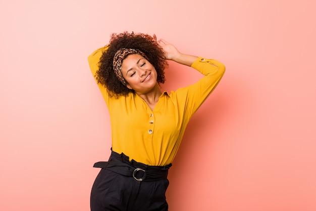 Młoda amerykanin afrykańskiego pochodzenia kobieta przeciw różowym rozciągania ramionom, zrelaksowana pozycja.