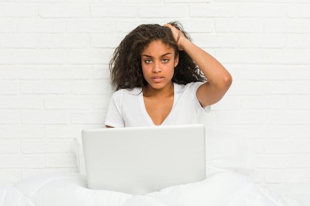 Młoda amerykanin afrykańskiego pochodzenia kobieta siedzi na łóżku z laptopem będąc w szoku, przypomniała sobie ważne spotkanie.