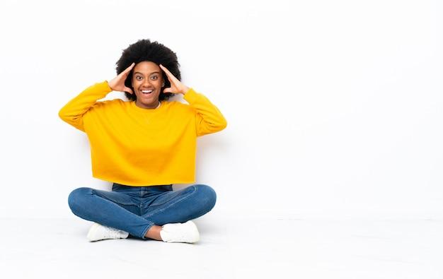 Młoda amerykanin afrykańskiego pochodzenia kobieta siedzi na podłoga z niespodzianki wyrażeniem