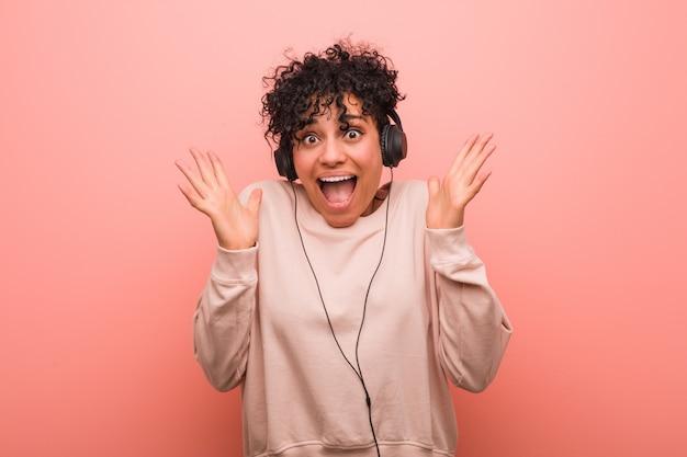 Młoda amerykanin afrykańskiego pochodzenia kobieta słucha muzyka świętuje zwycięstwo lub sukces