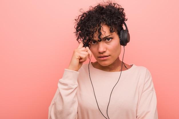 Młoda amerykanin afrykańskiego pochodzenia kobieta słucha muzyka wskazuje jego świątynię z palcem, myśleć, skupiający się na zadaniu.