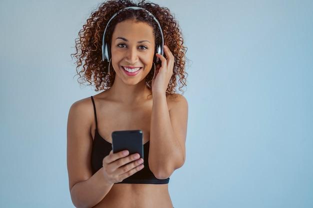 Młoda amerykanin afrykańskiego pochodzenia kobieta słucha ostrą muzykę używać bezprzewodowych hełmofony
