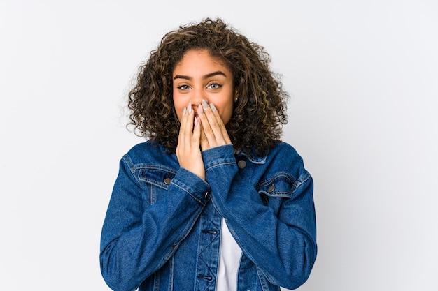 Młoda amerykanin afrykańskiego pochodzenia kobieta śmia się o coś, zakrywający usta rękami.