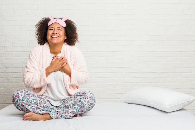 Młoda amerykanin afrykańskiego pochodzenia kobieta śmia się w łóżku pijama śmiać się utrzymujący ręki na sercu, pojęcie szczęście.