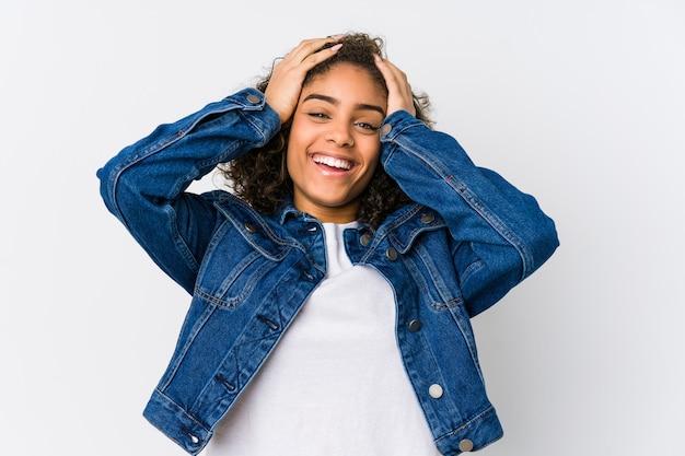 Młoda amerykanin afrykańskiego pochodzenia kobieta śmieje się z radością utrzymując ręce na głowie. koncepcja szczęścia.