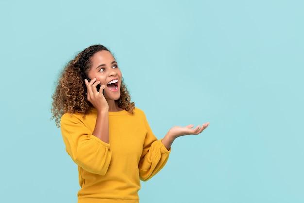 Młoda amerykanin afrykańskiego pochodzenia kobieta szczęśliwie zabiera do telefonu