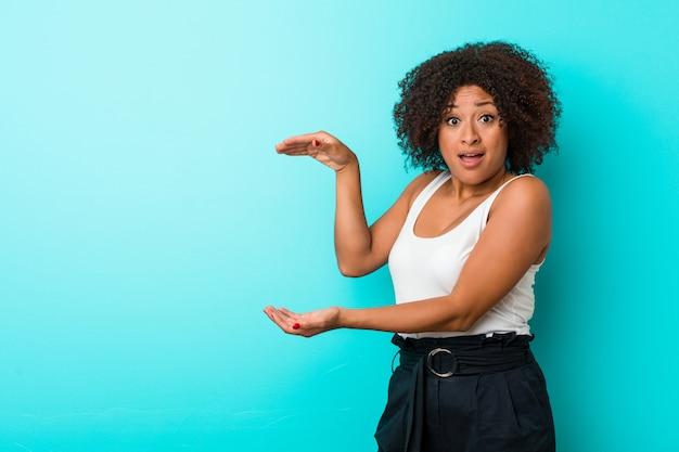 Młoda amerykanin afrykańskiego pochodzenia kobieta szokująca i zadziwiająca trzymająca odbitkową przestrzeń między rękami.