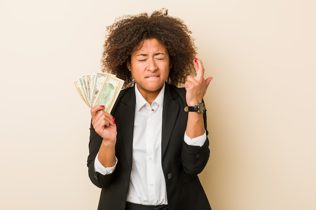 Młoda amerykanin afrykańskiego pochodzenia kobieta trzyma dolary krzyżuje palce dla mieć szczęście