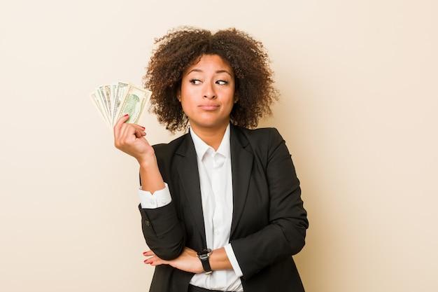 Młoda amerykanin afrykańskiego pochodzenia kobieta trzyma dolary patrzeje z ukosa z wątpliwym i sceptycznym wyrażeniem.