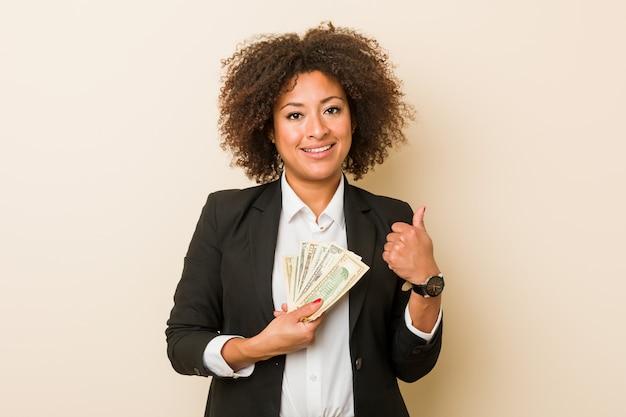 Młoda amerykanin afrykańskiego pochodzenia kobieta trzyma dolary uśmiecha się kciuk up i podnosi