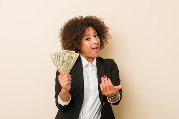 Młoda amerykanin afrykańskiego pochodzenia kobieta trzyma dolary wskazuje z palcem ciebie tak jakby zapraszający zbliżał się.