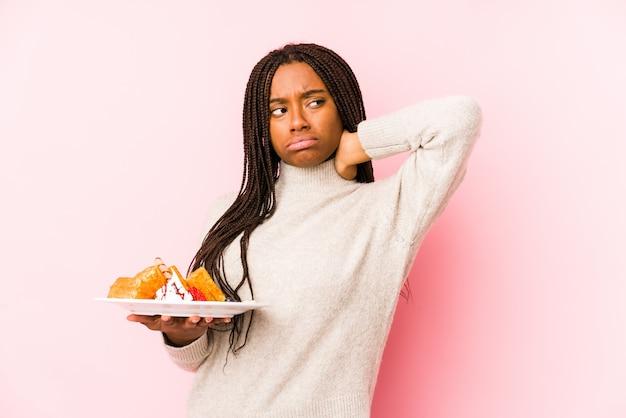 Młoda amerykanin afrykańskiego pochodzenia kobieta trzyma gofra odizolowywał macanie plecy głowę, myśleć i robi wyborowi.