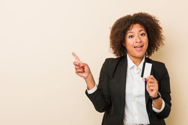Młoda amerykanin afrykańskiego pochodzenia kobieta trzyma kartę kredytową ono uśmiecha się radośnie wskazujący z palcem wskazującym daleko od.