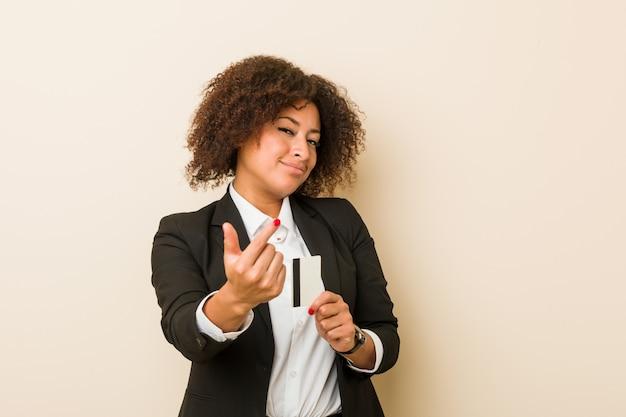 Młoda amerykanin afrykańskiego pochodzenia kobieta trzyma kartę kredytową wskazuje z tobą palcem, jakby zapraszający zbliżał się.