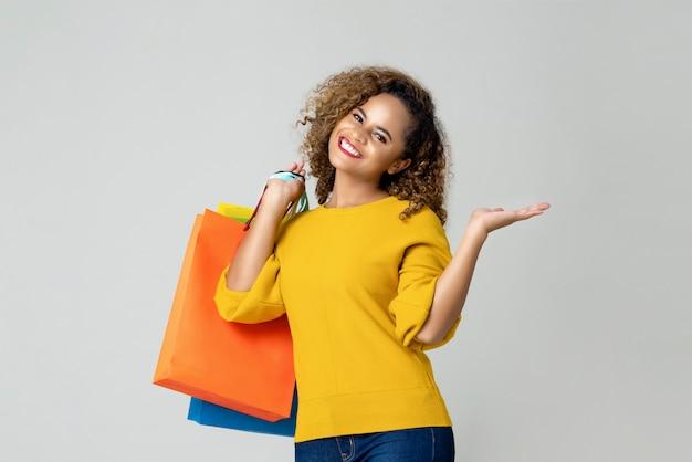Młoda amerykanin afrykańskiego pochodzenia kobieta trzyma kolorowych torba na zakupy