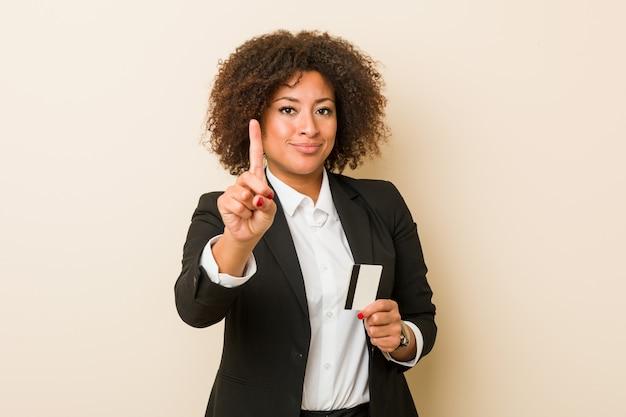 Młoda amerykanin afrykańskiego pochodzenia kobieta trzyma kredytową kartę pokazuje liczbę jeden z palcem.