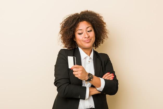 Młoda amerykanin afrykańskiego pochodzenia kobieta trzyma kredytowej karty ono uśmiecha się ufny z krzyżować rękami.
