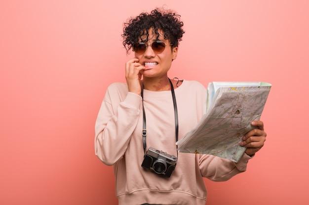 Młoda amerykanin afrykańskiego pochodzenia kobieta trzyma mapę obgryzający paznokcie, nerwowa i bardzo niespokojna.