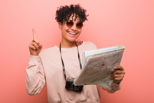 Młoda amerykanin afrykańskiego pochodzenia kobieta trzyma mapę pokazuje liczbę jeden z palcem.
