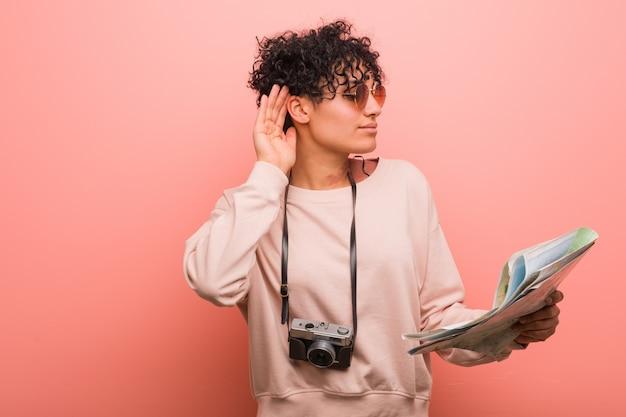 Młoda amerykanin afrykańskiego pochodzenia kobieta trzyma mapę próbuje słuchać plotki.
