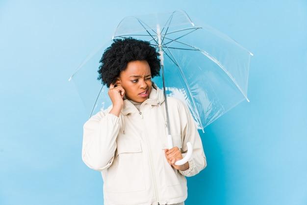 Młoda amerykanin afrykańskiego pochodzenia kobieta trzyma parasolowego nakrywkowego ucho z rękami.