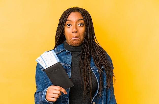 Młoda amerykanin afrykańskiego pochodzenia kobieta trzyma paszport odizolowywa wzrusza ramionami ramiona i otwiera oczy zmieszanych.