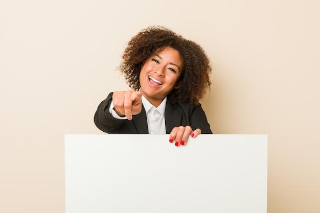 Młoda amerykanin afrykańskiego pochodzenia kobieta trzyma plakata rozochoconych uśmiechy wskazuje przód.