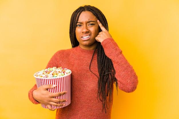 Młoda amerykanin afrykańskiego pochodzenia kobieta trzyma popcorn na białym tle pokazując gest rozczarowania palcem wskazującym.