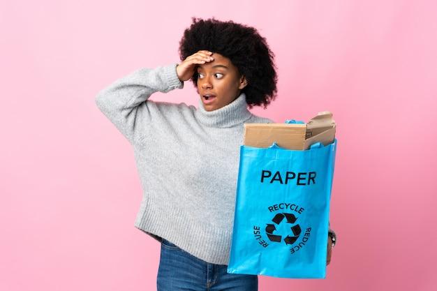 Młoda amerykanin afrykańskiego pochodzenia kobieta trzyma przetwarzającą torbę na kolorowej ścianie robi niespodzianka gestowi podczas gdy patrzejący strona